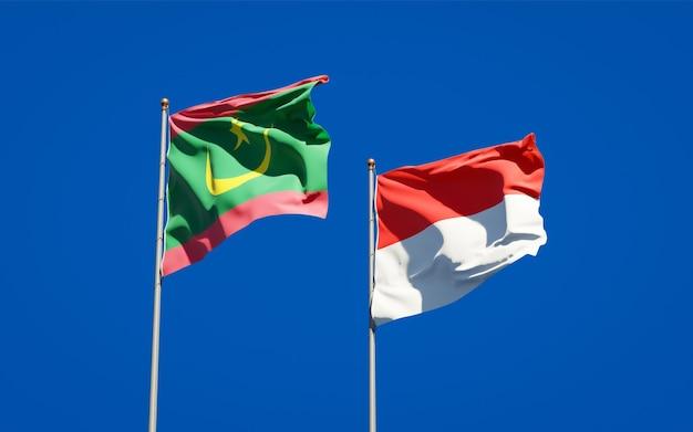 Piękne narodowe flagi państwowe mauretanii i indonezji razem na błękitnym niebie