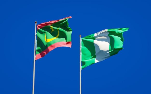 Piękne narodowe flagi państwowe mauretanii i nigerii razem na błękitnym niebie