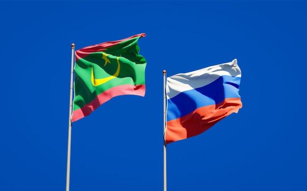 Piękne narodowe flagi państwowe mauretanii i rosji razem na błękitnym niebie. grafika 3d
