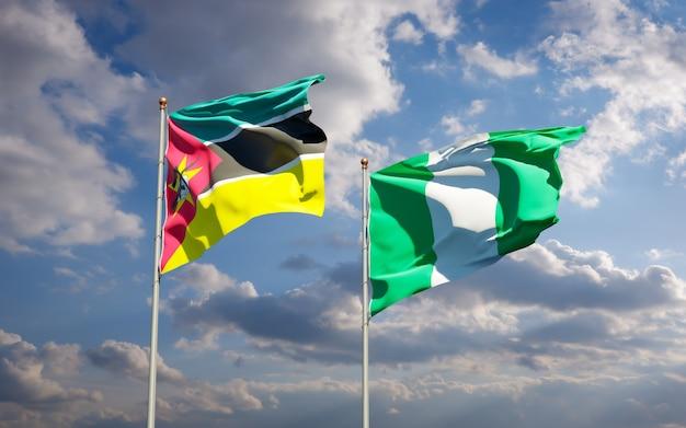 Piękne narodowe flagi państwowe mozambiku i nigerii razem na błękitnym niebie