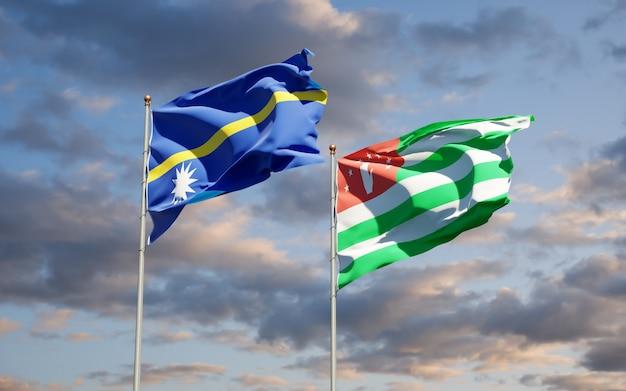Piękne narodowe flagi państwowe nauru i abchazji razem na błękitnym niebie. grafika 3d