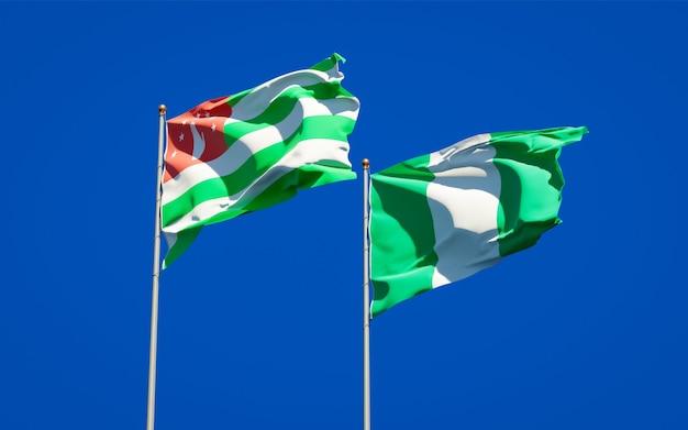 Piękne narodowe flagi państwowe nigerii i abchazji razem na błękitnym niebie