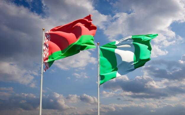 Piękne narodowe flagi państwowe nigerii i białorusi razem na błękitnym niebie