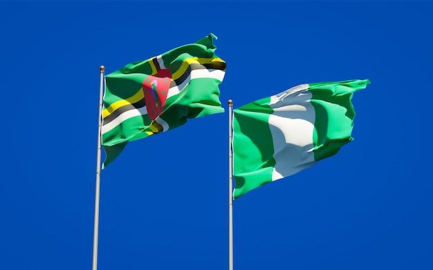 Piękne narodowe flagi państwowe nigerii i dominiki razem na błękitnym niebie