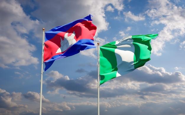 Piękne narodowe flagi państwowe nigerii i kambodży razem na błękitnym niebie