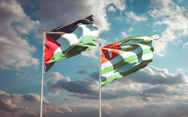 Piękne narodowe flagi państwowe palestyny i abchazji razem na błękitnym niebie. grafika 3d