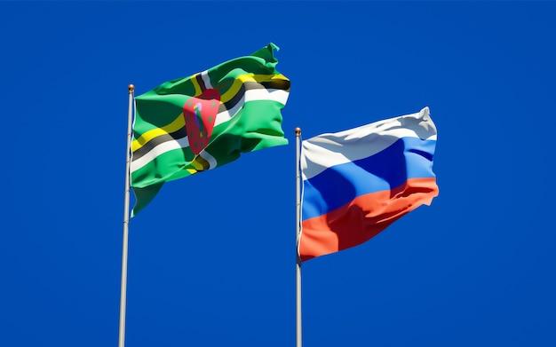 Piękne narodowe flagi państwowe rosji i dominiki razem na błękitnym niebie. grafika 3d