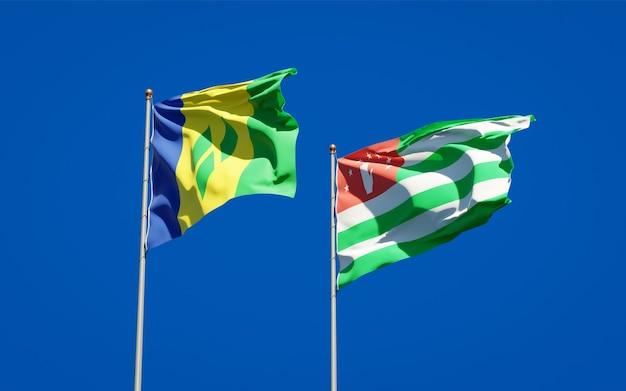 Piękne narodowe flagi państwowe saint vincent i grenadyny oraz abchazji razem na błękitnym niebie. grafika 3d