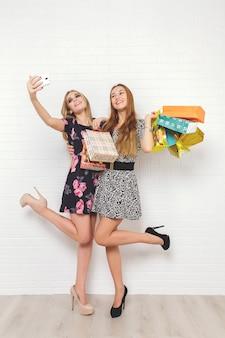 Piękne nastolatki niosące torby na zakupy