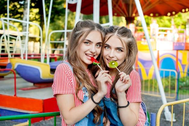Piękne nastoletnie bliźniaczki w kolorowych ubraniach z karmelowymi lizakami