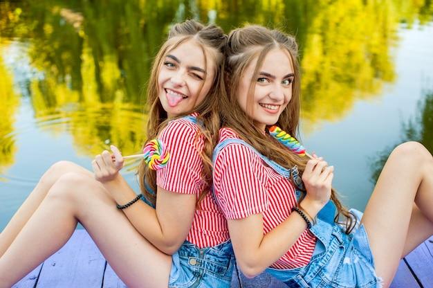 Piękne nastoletnie bliźniaczki w kolorowych ubraniach z lizakami siedzą na kolorowych deskach nad stawem