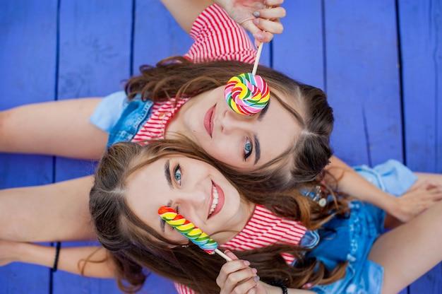 Piękne nastoletnie siostry bliźniaczki w kolorowe ubrania z lizakami siedzi na kolorowych deskach, widok z góry