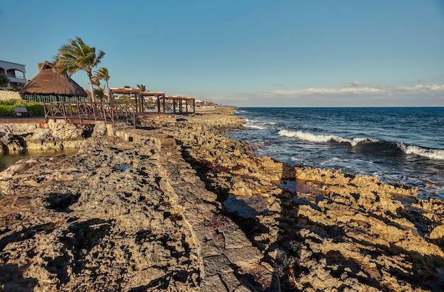 Piękne naturalne skaliste wybrzeże na skalistym wybrzeżu o zachodzie słońca w puerto aventuras w meksyku.