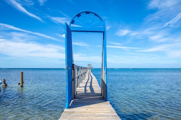Piękne niebieskie drzwi na drewnianym chodniku na karaibskiej wyspie roatan w hondurasie