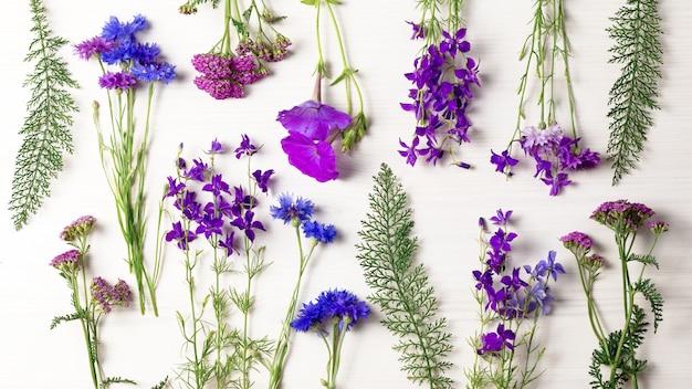 Piękne niebieskie i fioletowe kwiaty leżały płasko na białym drewnianym biurku