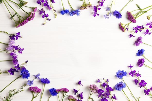 Piękne niebieskie i fioletowe kwiaty oprawione płasko leżały na białym drewnianym biurku