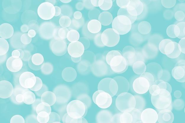 Piękne niebieskie tło z wieloma rozmytymi białymi światłami podobnymi do bokeh.