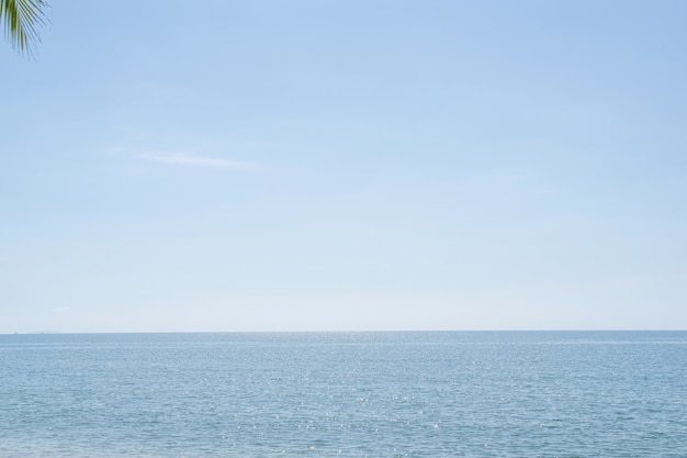 Piękne niebo nad morzem w słońcu. spokojna morska harmonia tafli wody. słoneczne niebo i niebieski ocean. wibrujący morze z chmurami na horyzoncie.