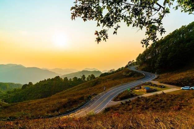 Piękne niebo zachód słońca z warstwą gór i dróg