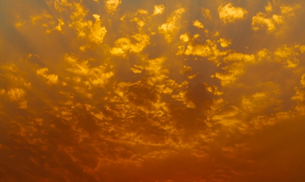 Piękne niebo zachód słońca. złote niebo zachód słońca z pięknym wzorem chmur. wieczorem pomarańczowe, żółte i czerwone chmury. wolność i spokój. piękno natury. potężna i duchowa scena.