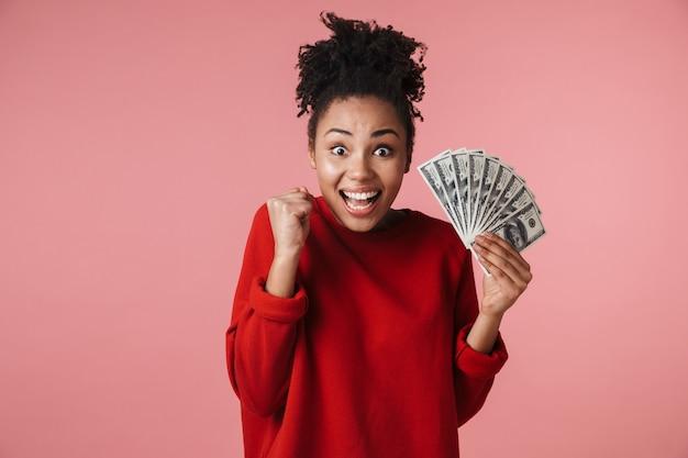 Piękne niesamowite szczęśliwy podekscytowany młoda afrykańska kobieta pozowanie na białym tle nad różową ścianą trzymając pieniądze zrobić gest zwycięzcy.
