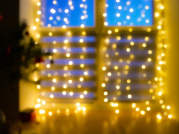 Piękne niewyraźne migoczące żółte światło. dekoracja domu z girlandami na oknie, nocne oświetlenie bokeh. świąteczne tło.