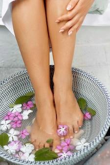 Piękne nogi kobiety i różne elementy spa. dobrze wypielęgnowane i pedicured paznokcie. masaż