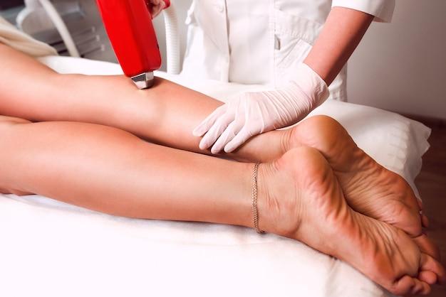 Piękne nogi kobiety na depilacji laserowej w gabinecie do depilacji i mistrzyni depilacji