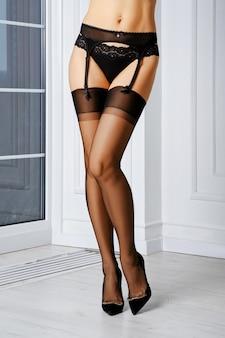 Piękne nogi kobiety w staromodnych pończochach bez elastanu, pasa do pończoch i majtek