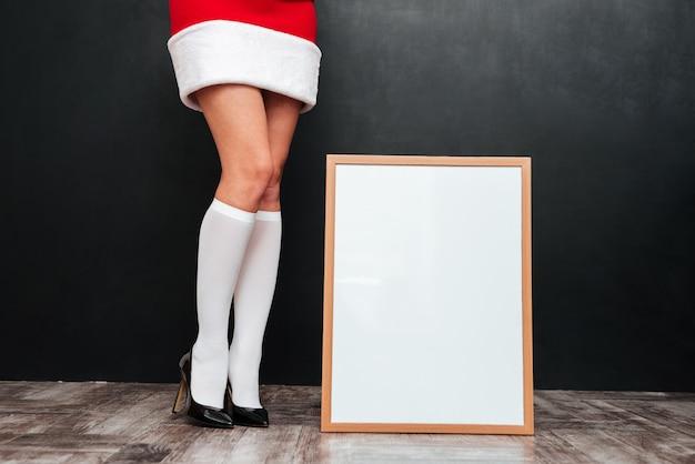 Piękne nogi młodej kobiety w stroju świętego mikołaja stojącej w pobliżu pustej białej tablicy na czarnej powierzchni