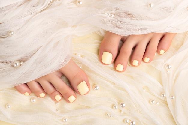 Piękne nogi womans z letnim wzorem paznokci na żółtym materiale