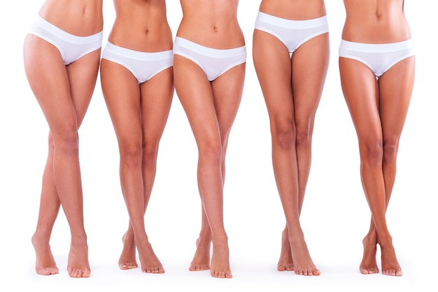 Piękne nogi. zbliżenie pięciu kobiet w majtkach i pokazujących idealne nogi, stojąc na białym tle