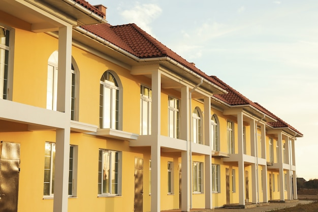 Piękne nowe żółte kamienice z czerwono - brązowym dachem