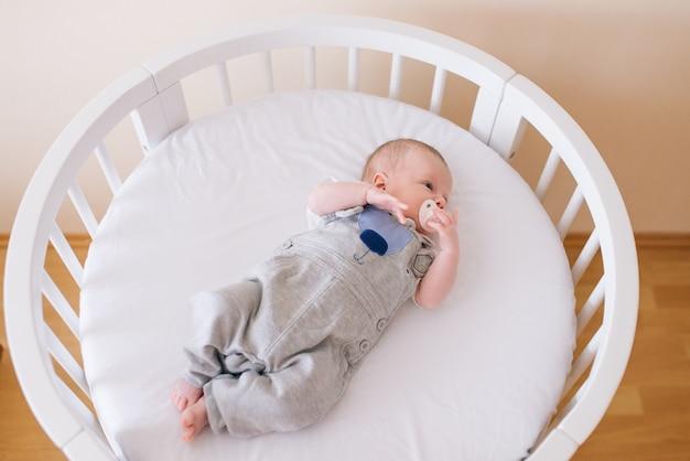 Piękne noworodek leżący w okrągłym łóżku z pięknymi zderzakami w delikatnych odcieniach szarości, błękitu i bieli