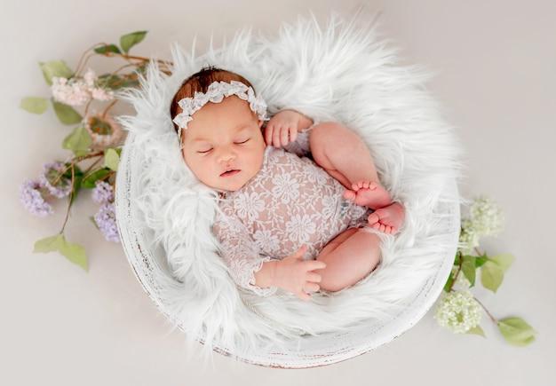 Piękne noworodka dziewczynka sobie koronkowy kostium an wieniec spanie w dorzeczu wypełnione białe futro podczas sesji zdjęciowej w studio. śliczny portret drzemiącego niemowlęcia