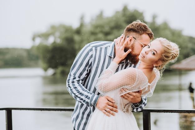 Piękne nowożeńcy pozują na pomoście, a pan młody delikatnie przytula i całuje pannę młodą w szyję na nabrzeżu.