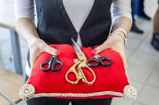 Piękne nożyczki na czerwonej poduszce w rękach kobiet