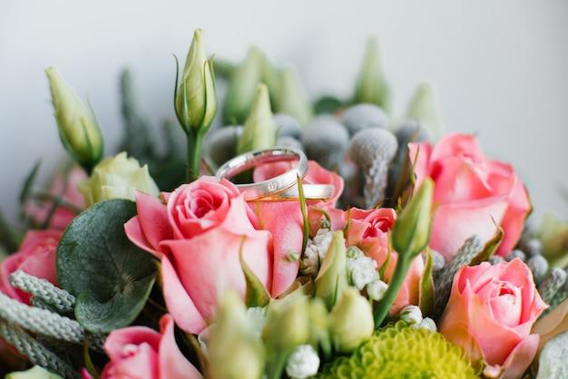 Piękne obrączki ślubne kłamają na kwiatach, zakończenie. szczegóły ślubu
