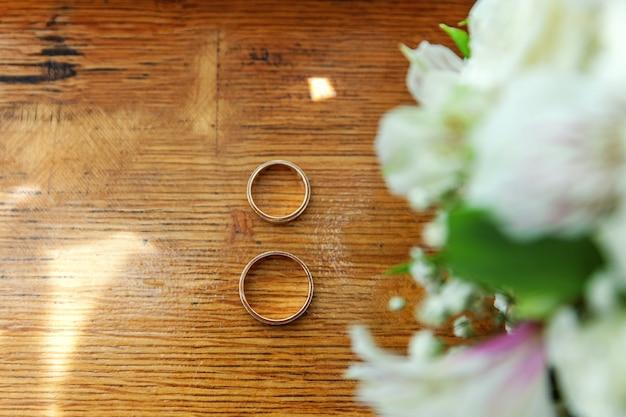 Piękne obrączki ślubne leżą na drewnianej powierzchni na tle bukiet kwiatów.