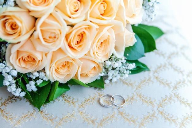 Piękne obrączki ślubne leżą na jasnej powierzchni na tle bukietu kwiatów.