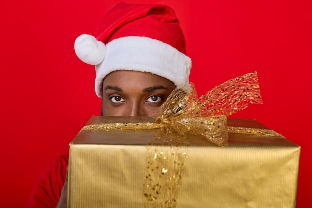 Piękne oczy czarnoskórego mężczyzny w czapce mikołaja wychodzą zza dużego świątecznego prezentu