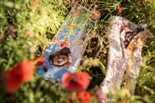 Piękne odbicie dziewczyny w lustrze na polu maku. czas letni