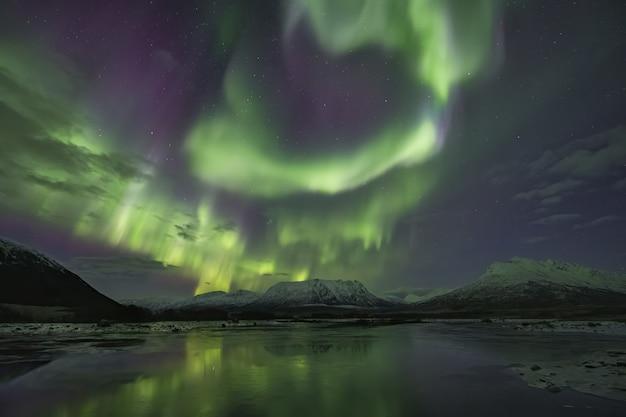 Piękne odbicie zorzy polarnej w jeziorze otoczonym ośnieżonymi górami