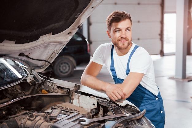 Piękne oświetlenie. pracownik w niebieskim mundurze pracuje w salonie samochodowym.