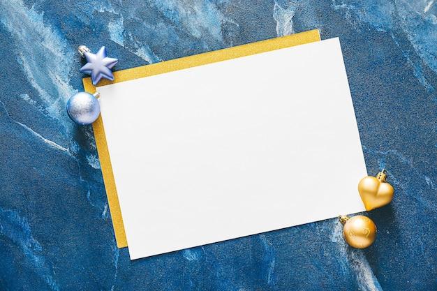 Piękne ozdoby świąteczne z pustą kartą na niebieskim marmurowym stole
