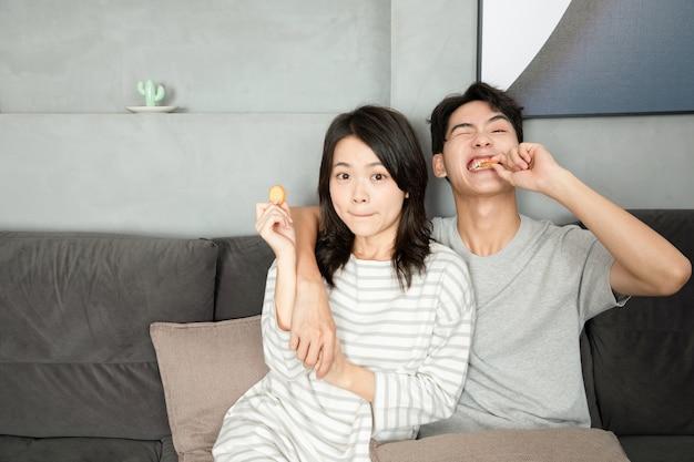 Piękne pary odpoczywają i jedzą przekąski w domu