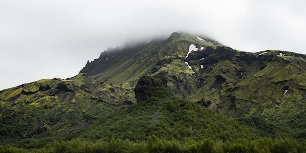 Piękne pasmo górskie pokryte śniegiem spowitym mgłą - idealne na naturalną tapetę