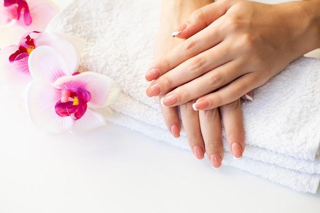 Piękne paznokcie kobiety z francuskim manicure, w studio urody
