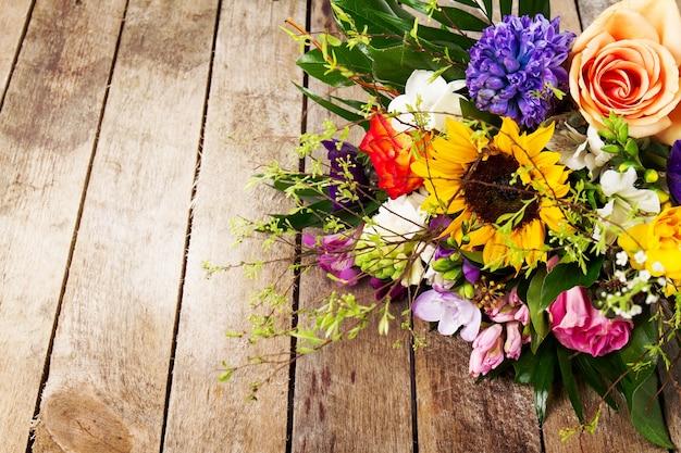 Piękne pęczek kwiatów na tle drewniane. poziomy. widok z góry.