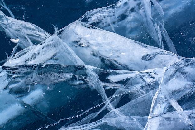 Piękne pęknięcia w gęstym, czystym lodzie jeziora. niebieski przezroczysty lód z białymi pęknięciami. poziomy.